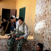 Young rebel fighters take a rest after a hours battling to take control of the village Bir Jaiyad.