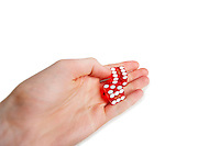 Cropped image of hands holding gambling cubes over white background