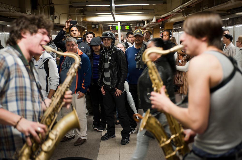 Moon Hooch, eine junge Band aus Brooklyn, mit ihrem upbeat funky jazz sound auf der L train Plattform im Union Spquare Station...Jedes Jahr im Mai laden die Betreiber der New Yorker Subway (MTA) ca 60 Musiker und Gruppen zu einem Wettbewerb im Grand Central Station ein. Die Gewinner duerfen ganz legal an ihnen zugeteilten Orten im Ubahn System auftreten. Viele unangemeldete  und selbst organisierte Musiker jeder nur erdenklichen Musikrichtung spielen zudem in fast jeder wichtigen Ubahnstation. Die Angst vor der Polizei ist dabei gering, selten gibt es eine Verwarnung und noch seltener ein Bussgeld. Meist wird einfach der Ort gewechselt falls es Probleme gibt...Moon Hooch, a Brooklyn-based collaborative trio, play their upbeat funky jazz sound on the L train platform at Union Square.Music Under New York.Auditions.Every Spring, Music Under New York (MUNY) presents a day of auditions in Grand Central Terminal to review and add new performers to the MUNY roster. This year, MUNY held its annual auditions in May on the Northeast Balcony of the Grand Central Terminal. .In addition legions of non-official musicians play in New Yorks subway stations and on platforms. One can find every thinkable style and instrument underground. ..Foto: Stefan Falke.