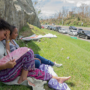 SEPTEMBER 25 - RIO GRANDE, PUERTO RICO - <br /> Kiara Rodriguez de Jesus, 23, and friend Stephanie Norat, 26, find shade as people wait in line at the Gulf Route 66 gas station for a gasoline tanker scheduled to arrive with fuel sometime today. People have been waiting in line inside cars and on foot with gas canisters since before sunrise and the line of cars extended close to one mile.<br /> (Photo by Angel Valentin for NPR)