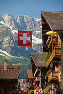 The alpine village of Champéry, Switzerland, in the canton of Valais. A Swiss flag hangs over the street.