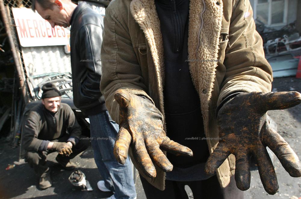 Die Hände eines Automechanikers in seinen Handschuhen. Auf dem Eliawabasar in Tiflis verkaufen die Händler Einzelteile aus dem Schrott alter Autos. (The glove-protected hands of a car mechanic. At the Eliawa Market selling dealer parts of old damaged cars.)