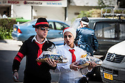"Orthodox couple in Purim costume with Mishloach manot. Photographed in Bnei Brak, Israel. Mishloach manot (literally, ""sending of portions"") also called a Purim basket, are gifts of food or drink that are sent to acquaintances on Purim day"