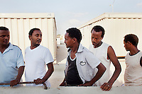 "Hal Far, Malta - 19 August, 2012: Ethiopian immigrants stand in front of the containers of the Hal Far Tent Village open centre they live in, in Hal Far, Malta, on 19 August, 2012.The Hal Far Tent Village, initially composed of tents when it first opened, is composed today of 100 containers with no water where the immigrants live for months, and sometimes years. Hal Far (which translates as ""Rat's Town"") is an industrial area of Malta which hosts two open centres for immigrants.  The open centres in Malta serve as a temporary accomodation facility, but they ended becoming permanent accomodation centres, except for those immigrants who receive subsidiary protection or refugee status and that are sent to countries such as the United States, Germany, Poland, and others. All immigrants who enter in Malta illegally are detained. Upon arrival to Malta, irregular migrants and asylum seekers are sent to one of three dedicated immigration detention facilities. Once apprehended by the authorities, immigrants remain in detention even after they apply for refugee status. detention lasts as long as it takes for asylum claims to be determined. This usually takes months; asylum seekers often wait five to 10 months for their first interview with the Refugee Commissioner. Asylum seekers may be detained for up to 12 months: at this point, if their claim is still pending, they are released and transferred to an Open Center.<br /> Gianni Cipriano for The New York Times"