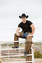rugged cowboy sitting on a fence