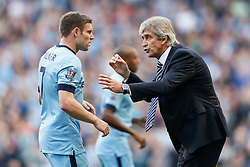 Manager Manuel Pellegrini of Manchester City talks to James Milner - Photo mandatory by-line: Rogan Thomson/JMP - 07966 386802 - 21/08/2014 - SPORT - FOOTBALL - Manchester, England - Etihad Stadium - Manchester City v Chelsea FC - Barclays Premier League.