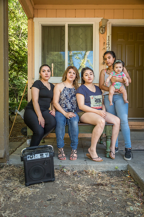 Yessica Lopez, Silvia Romero, Heydy Romero, Jasmin Lopez and one year old Isabel Guerrero, sit on the porch of their house in Calistoga.