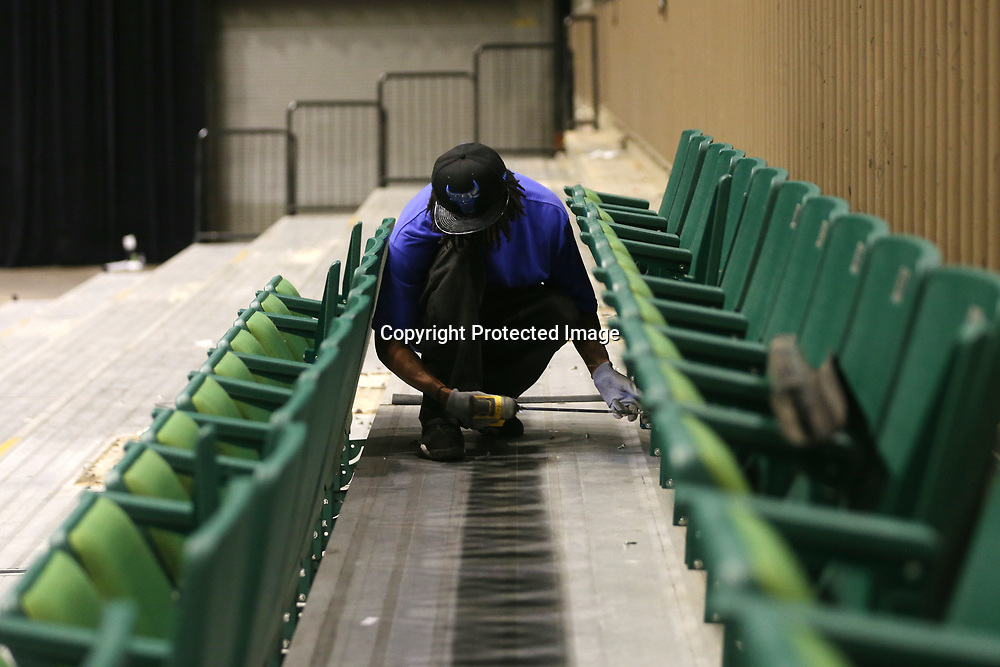 Jonathan Lambert unscrews a row of seats as he and a crew work on removing the lower bowl at the BancorpSouth Arena Tuesday morning.