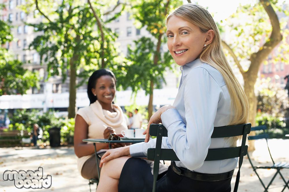 Female colleagues sitting at street cafe