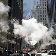 Steam rises from a vent near Wall Street in the Financial District, Downtown Manhattan,  New York City, USA. 16th September 2014. Photo Tim Clayton