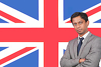 Portrait of young businessman with arms crossed over British flag