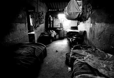IPMG0094 South Africa, Thokoza, 1990..A room inside the Mshaya'zafe hostel in Tokoza on the East Rand some 20km East of Johannesburg, August 17, 1990. The migrant workers' hostel was later destroyed in the clashes between Inkatha Freedom Party supporters and those of the African National Congress. Thousands of people, both civilians and combatants died in the so-called Hostel War from 1989-1995..Photograph by Greg Marinovich/South Photographs
