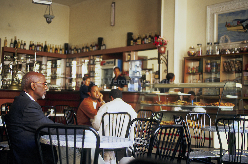 Drinking italian expressos and eating pastries in a cafe of Asmara, Eritrea // Asmara est la capitale et la plus grande ville de l'Erythree. Sa population est d'environ 500,000 habitants.Asmara se forma a partir de quatre villages au XIIe siecle comme relais. Elle devint plus tard la capitale du prince Ras Alula. Elle fut colonisee par l'Italie en 1889 et devint la capitale nationale en 1897. Vers la fin des annees 30, les italiens modifierent profondement la ville avec un nouvel ordonnancement et de nouveaux batiments; Asmara etait appelee -Piccola Roma- (la petite Rome). De nos jours, la plupart des batiments sont d'origine italienne. Le cafe fait partie de la vie quotidienne de la ville d'Asmara. On y boit des expressos et on y mange des pizzas...