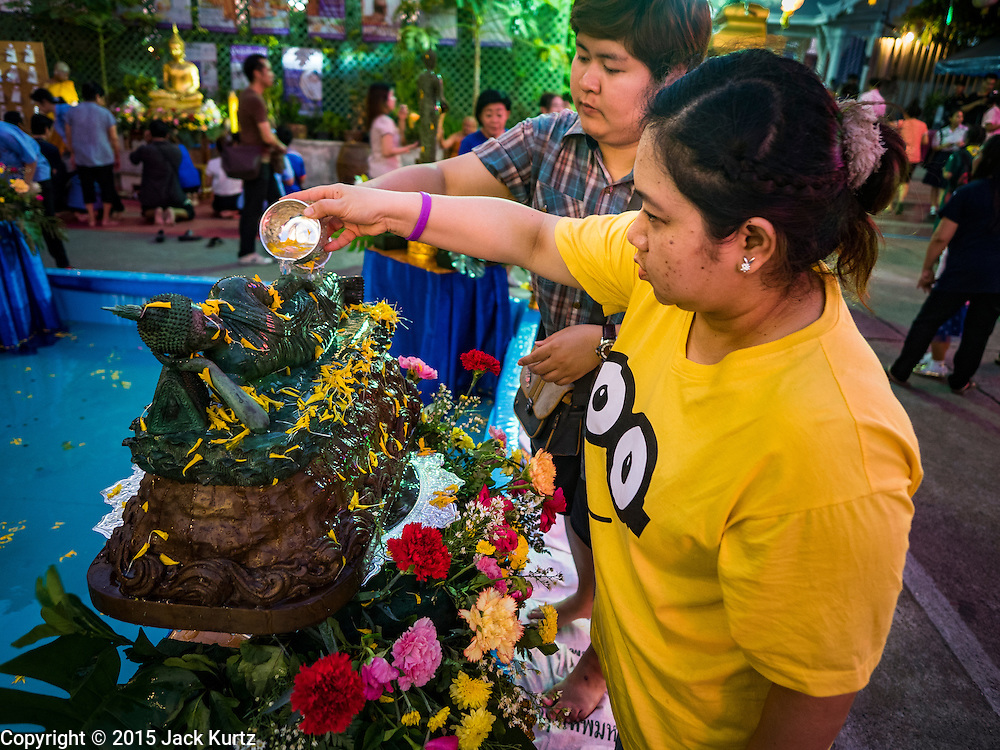 25 NOVEMBER 2015 - BANGKOK, THAILAND: Thais bathe a Buddha statue during Loy Krathong at Wat Yannawa in Bangkok. Loy Krathong takes place on the evening of the full moon of the 12th month in the traditional Thai lunar calendar. In the western calendar this usually falls in November. Loy means 'to float', while krathong refers to the usually lotus-shaped container which floats on the water. Traditional krathongs are made of the layers of the trunk of a banana tree or a spider lily plant. Now, many people use krathongs of baked bread which disintegrate in the water and feed the fish. A krathong is decorated with elaborately folded banana leaves, incense sticks, and a candle. A small coin is sometimes included as an offering to the river spirits. On the night of the full moon, Thais launch their krathong on a river, canal or a pond, making a wish as they do so.     PHOTO BY JACK KURTZ