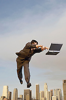 Business man reaching for laptop mid-air above city
