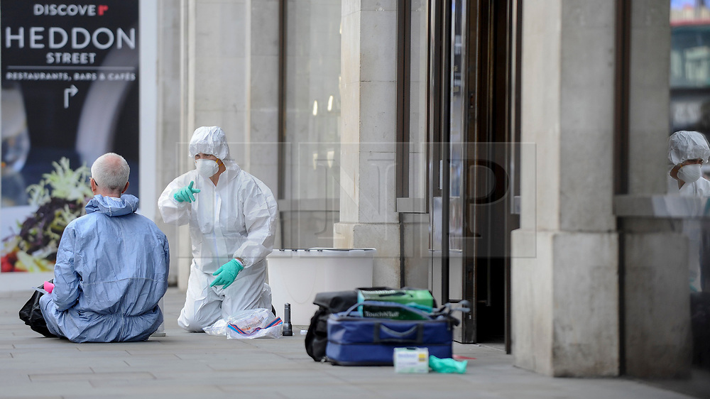 © Licensed to London News Pictures. 05/06/2018. LONDON, UK.  Members of a forensics team examine the scene in and outside the Watches of Switzerland store on Regent Street.  Two motorcycles were involved in a smash and grab incident at the premises.  Investigations are ongoing.  Photo credit: Stephen Chung/LNP