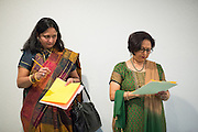 Vaidehi Parekh of Evergreen, left, takes a peek at Mita Vora's scorecard, of Fremont, while they judge the Diwali Rangoli competition at the Shreemaya Krishnadham Temple in Milpitas, California, on November 2, 2013. (Stan Olszewski/SOSKIphoto)