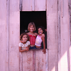 Three little girls smiling on a window in Brazil.