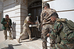 © Licensed to London News Pictures. 09/03/2015. Erbil, Iraq. Kurdish peshmerga fighters use a battering ram to forcibly enter a building during training run by German soldiers at a partially finished housing estate near Erbil, Iraq. <br /> <br /> The training is part of a four week platoon level infantry training package run by coalition forces aimed at improving the efficiency of the Iraqi Security Forces. Photo credit: Matt Cetti-Roberts/LNP