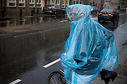 Een vrouw op de fiets wacht met een stuk regenponcho in haar mond in de stromende regen tot ze over kan steken.<br /> <br /> A woman on a bike is waiting in the rain to cross the street.