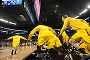 The University of Michigan Wolverines rush the court after defeating the University of Kansas Jayhawks in the NCAA South Regionals at Cowboys Stadium in Arlington on Friday, March 29, 2013. (Cooper Neill/The Dallas Morning News)