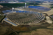 A view of the Andasol 1 and 2, a parabolic through power plants located in Granada, Spain. With a gross electricity output of around 180 GWh per year and a collector surface area of over 510, 000 square meters - equal to 70 soccer pitches - they are the largest solar power plants in the world..Following their construction period of around two years, the Andasol power plants will supply up to 200,000 people with environmentally friendly solar electricity. Photographer: Markel Redondo/Fedephoto.com for Greenpeace.Site de la tour PS10 de la centrale solaire de Sanlucar la Mayor, pres de Seville, Espagne. La centrale solaire, la premiere centrale commerciale au monde, appartenant a la societe espagnole Solucar (Abengoa), peut produire de l'electricte pour 6000 habitations. Solucar (Abengoa) projete de construire un total de 9 nouvelles tours dans les 7 ans qui viennent, afin de fournir 180 000 habitations en electricite. Photographe: Markel Redondo/Fedephoto pour Greenpeace...The PS10 solar tower plant sits at Sanlucar la Mayor outside Seville, Spain. The solar tower plant, the first commercial solar tower in the world, by the Spanish company Solucar (Abengoa), can provide electricity for up to 6,000 homes. Solucar (Abengoa) plans to build a total of 9 solar towers over the next 7 years to provide electricity for an estimated 180,000 homes. Photographer: Markel Redondo/Fedephoto for Greenpeace.