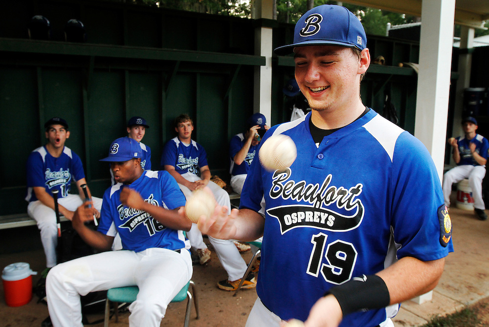Beaufort High School baseball player Alex Tokar, juggles some baseballs as teammates react to a lightning strike during a weather delay in a game against Goose Creek High School at Beaufort High School on June 26, 2014.