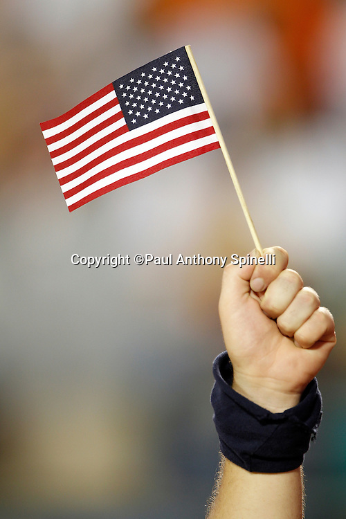 A Miami Dolphins fan holds an American flags during the playing of the National Anthem at the NFL week 1 football game against the New England Patriots on Monday, September 12, 2011 in Miami Gardens, Florida. The Patriots won the game 38-24. ©Paul Anthony Spinelli