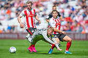 Andy Cannon (#14) of Portsmouth FC is tackled by Lynden Gooch (#11) of Sunderland AFC during the EFL Sky Bet League 1 match between Sunderland and Portsmouth at the Stadium Of Light, Sunderland, England on 17 August 2019.