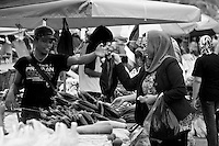 A muslim woman purchases vegetables at the waterfront market in Kota Kinabalu.