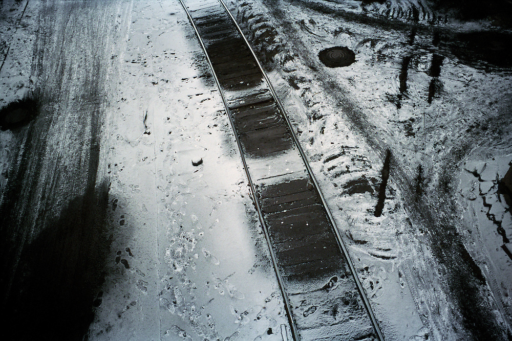 Railway tracks inside a steel plant. Snow mixes with fly ash that settles on the ground from the plant. Benxi, China. 2007