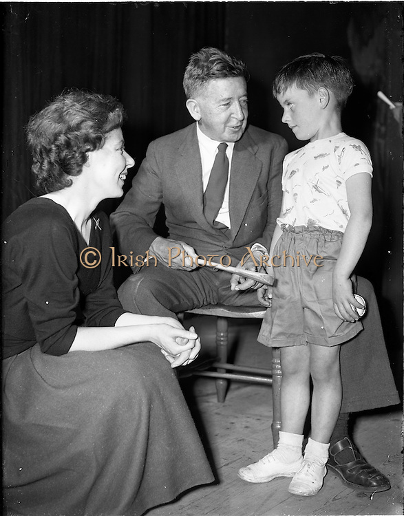 27/05/1959<br /> 05/27/1959<br /> 27 May 1959<br /> Gael-Linn Concert and Singing Competition in the Town Hall, Nenagh, Co. Tipperary, in which R.E. singers and harpists took part. Image shows Mr J.P. Flynn, Tipperary County Manager, admiring Mairtin Misteal's hurley, which he received as a prize-winner in the competition. Included is Mr Flynn's daughter Deirdre, Radio Eireann harpist and singer, who sang at the concert.
