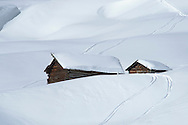 Two old wooden barns surrounded by deep snow and ski tracks in the Dolomites, South Tyrol, Italy