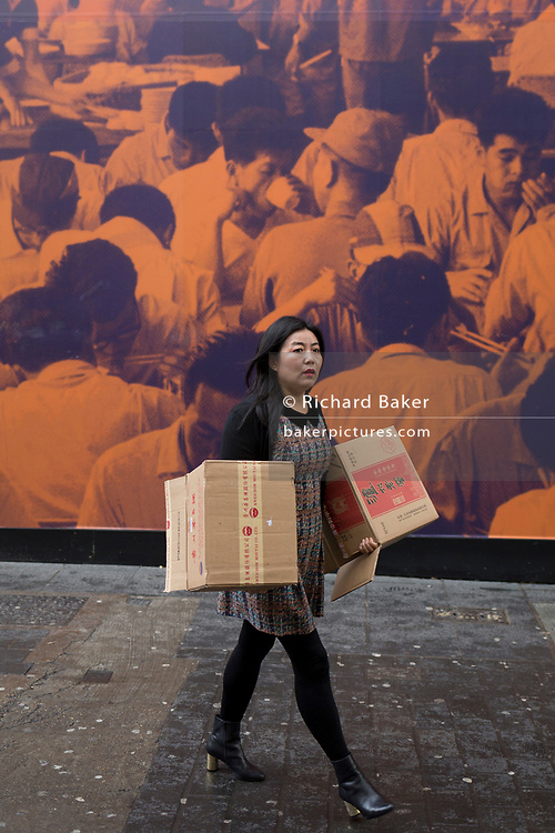 A Chinese lady carries boxes and walks in front of a construction hoarding featuring Asian canteen people in Chinatown, on 8th March 2017, London borough of Westminster, England.