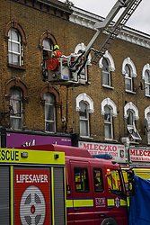 © Licensed to London News Pictures. 01/04/2020. London, UK. Aerial platform operated by the London Fire Brigade. In an incident involving all emergency services a suspected COVID-19 case is isolated and removed from home. Uxbridge Road in Shepherd's Bush was closed for an hour as ambulance, fire brigade and police attended, extracting the patient by crane from a three story apartment building in West London. PPE (personal protective equipment) was in evidence, with the fire brigade using full face respirators normally reserved for firefighting. A police officer commented the Metropolitan police force are issued only with rubber gloves. Ambulance workers decontaminated the scene and reusable equipment before moving on.  Photo credit: Guilhem Baker/LNP