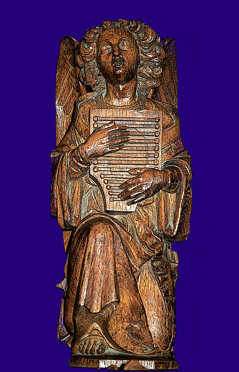 Carved wood musical angel in choir stall of an English cathedral.  Cutout from photo with purple background added.