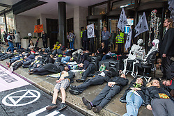 London, UK. 19 July, 2019. Climate activists from Extinction Rebellion take part in a 'Requiem For A Dead Planet: Newspapers Tell The Truth' event outside the offices of the Daily Mail, Mail on Sunday, Evening Standard and Independent newspapers in Kensington on the fifth day of their 'Summer Uprising' to call for the media to 'tell the truth' regarding the climate crisis, to cease publishing articles by discredited climate change deniers and advertising and editorial promoting a high-carbon lifestyle and to declare a climate emergency.