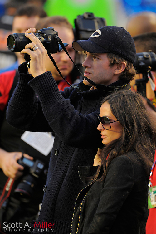 Miami, FL, USA; Miami, FL, USA; Feb 7, 2010; Actor Ashton Kutcher, left looks though his Nikon camera with his wife actress Demi Moore at his side prior to Super Bowl XLIV at Sun Life Stadium. The New Orleans Saints 31-17 beat the Indianapolis Colts..©2010 Scott A. Miller
