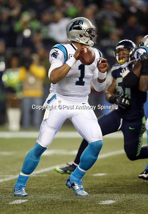 Carolina Panthers quarterback Cam Newton (1) drops back and a late second quarter pass for a first down during the NFL week 19 NFC Divisional Playoff football game against the Seattle Seahawks on Saturday, Jan. 10, 2015 in Seattle. The Seahawks won the game 31-17. ©Paul Anthony Spinelli