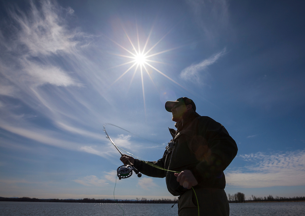 "angler casting on lake champlain with a ""sunstar"" overhead"