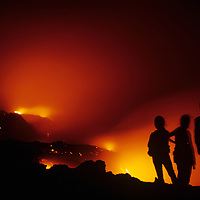 USA, Hawaii, Volcanoes National Park,  Tourists watch as molten lava flows from Kilauea volcano into ocean at night