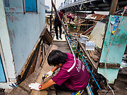 14 NOVEMBER 2017 - BANGKOK, THAILAND:  City workers tear down homes along the Chao Phraya River south of Krung Thon Bridge to make way for the city's plan to build a 14 kilometer long (22 mile) riverfront promenade. The city also maintains that the homes interfere with navigation on the river and pose a health a safety hazard because they are prone to seasonal flooding. Thousands of families are expected to be evicted to accommodate the promenade. The riverside communities, built on stilts over the water, are prone to flooding and the city has been trying to control them for years. The houses are the only affordable housing for available to some of the poorest people in Bangkok.  PHOTO BY JACK KURTZ