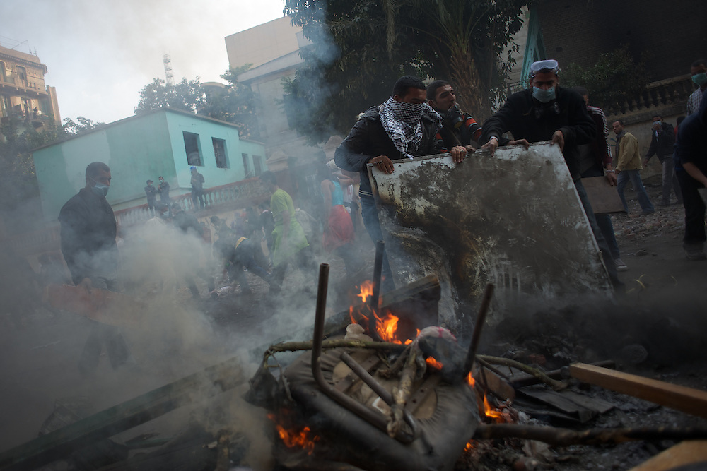 Egyptian protestors clean the rubble from a road to allow ambulances to pass collect people injured during violent clashes with the security forces.