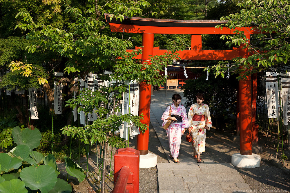 Two girls wearing yukata, passing under the tori gate at Tsurugaoka Hachimangu shrine in Kamakura