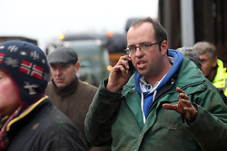 © Licensed to London News Pictures. Moorland. Somerset. 06/02/14. Owner of farm James Winslade (portrait) green top on phone. West Yeo farm - The evacuation of 550 beef cattle all in a day. Rebecca Horsington put out an appeal on Facebook for help today- about 30 farmers arrived with trailers to take cattle toa nearbycattle market in Bridgwaterout of danger. from floodwater which was rising rapidly.. Photo credit : Jason Bryant/LNP