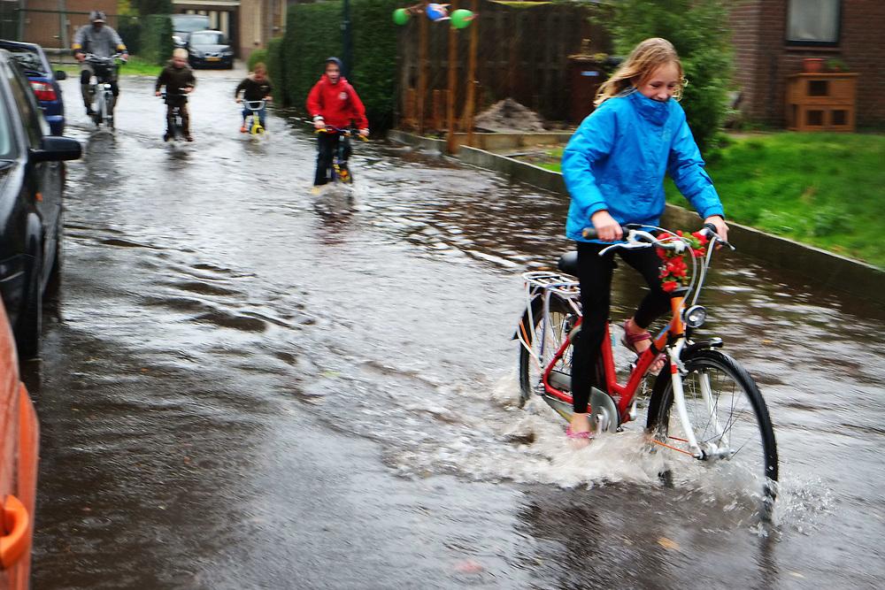 Nederland, Kockengen, 13 okt 2013<br /> Doordat de bodem inklinkt en verzakt staan de straten in Kockengen al snel vol met plassen. Met de hevige regenval op zondag was het wel heel erg.  Voor kinderen betekende het wel weer extra pret. <br /> Foto(c): Michiel Wijnbergh