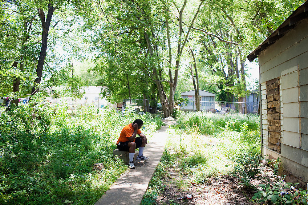 Carlos sits by himself smoking a blunt in the shade of one of the abandoned alleyways of the Baptist Town neighborhood of Greenwood, Mississippi on May 28, 2011.