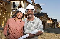Middle-aged couple holding blueprints at construction site, portrait