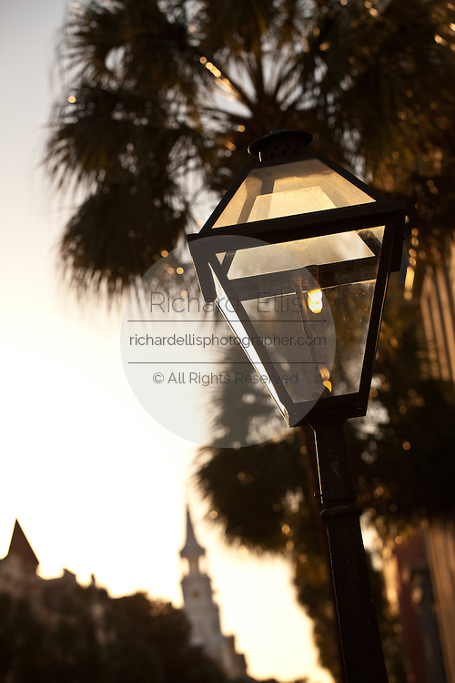 A gas lamp with St Michael's Church in Charleston, SC.
