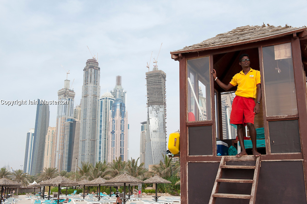 Lifeguard on duty at Jumeirah Beach with high rise apartment buildings at Dubai Marina to rear in Dubai United Arab Emirates , UAE